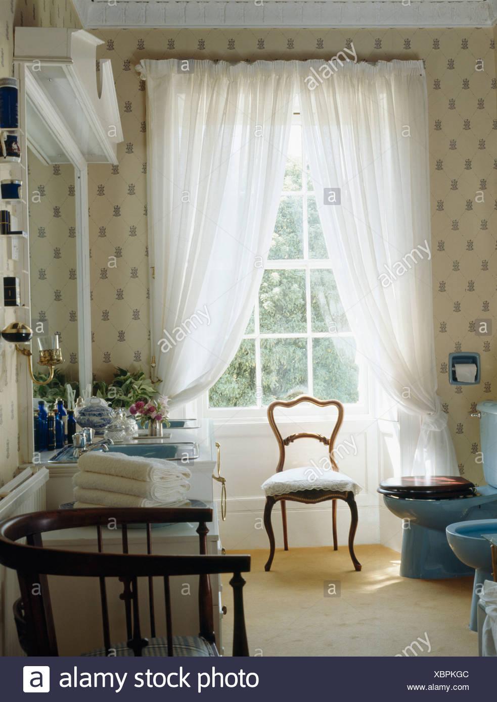 Silla antigua delante de grandes ventanales con cortinas de velo ...