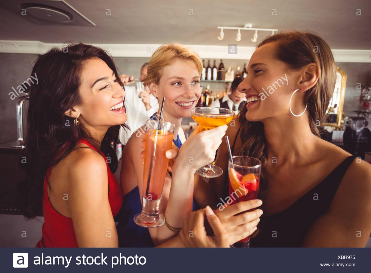 Feliz amigas sosteniendo un vaso de cóctel Imagen De Stock