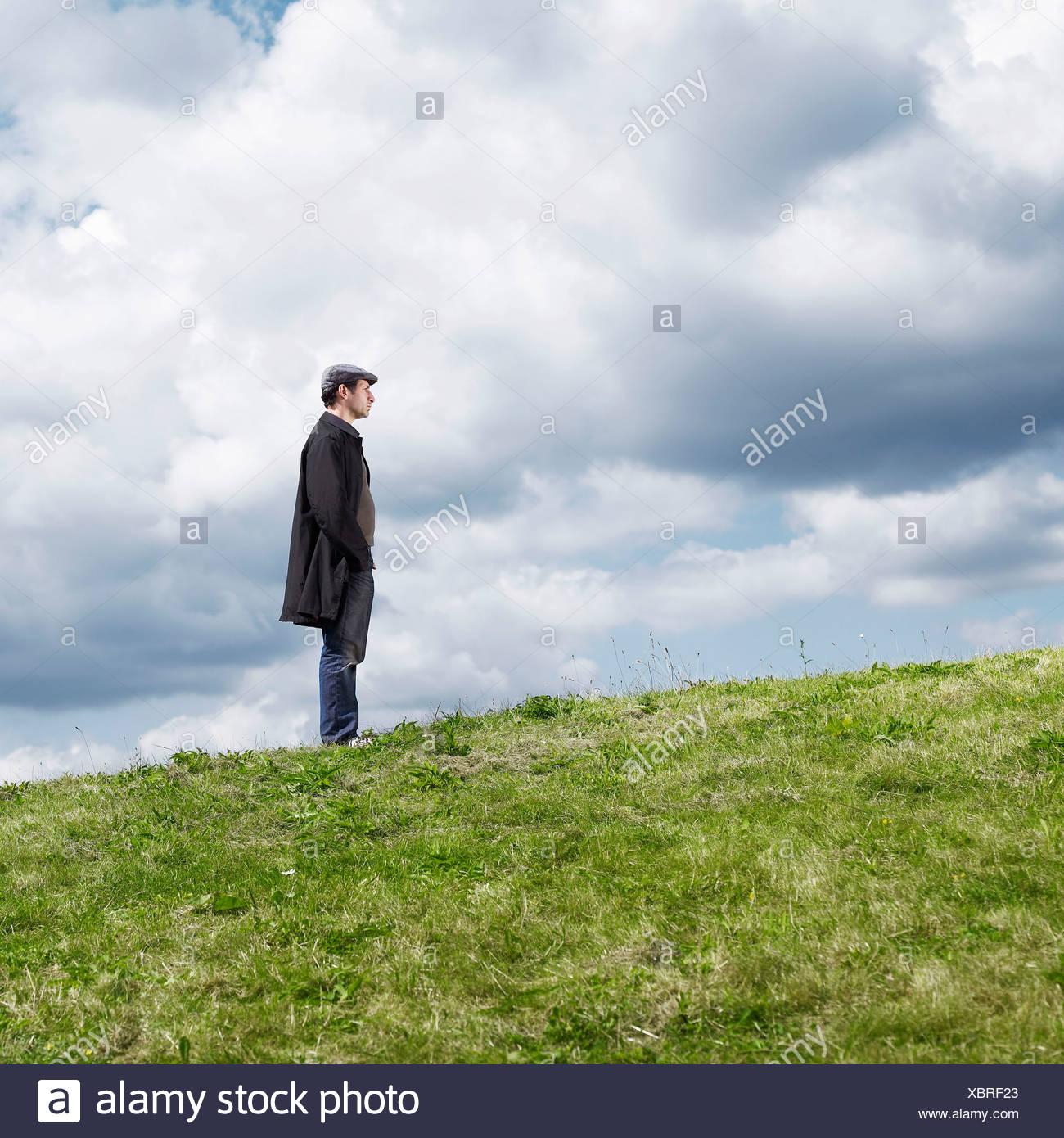 Hombre de pie en la colina solitaria Foto de stock