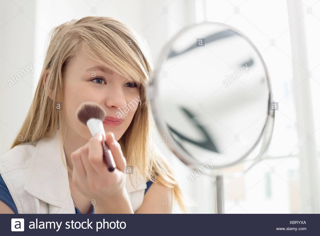 Chica al maquillaje delante del espejo en casa Imagen De Stock