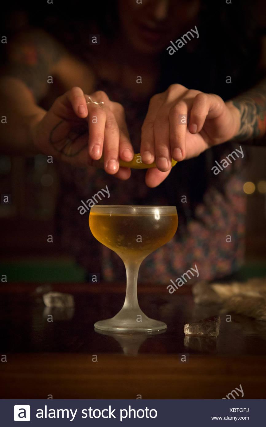 Las manos de una mujer exprimir una rodaja de limón en un vaso de cóctel. Foto de stock