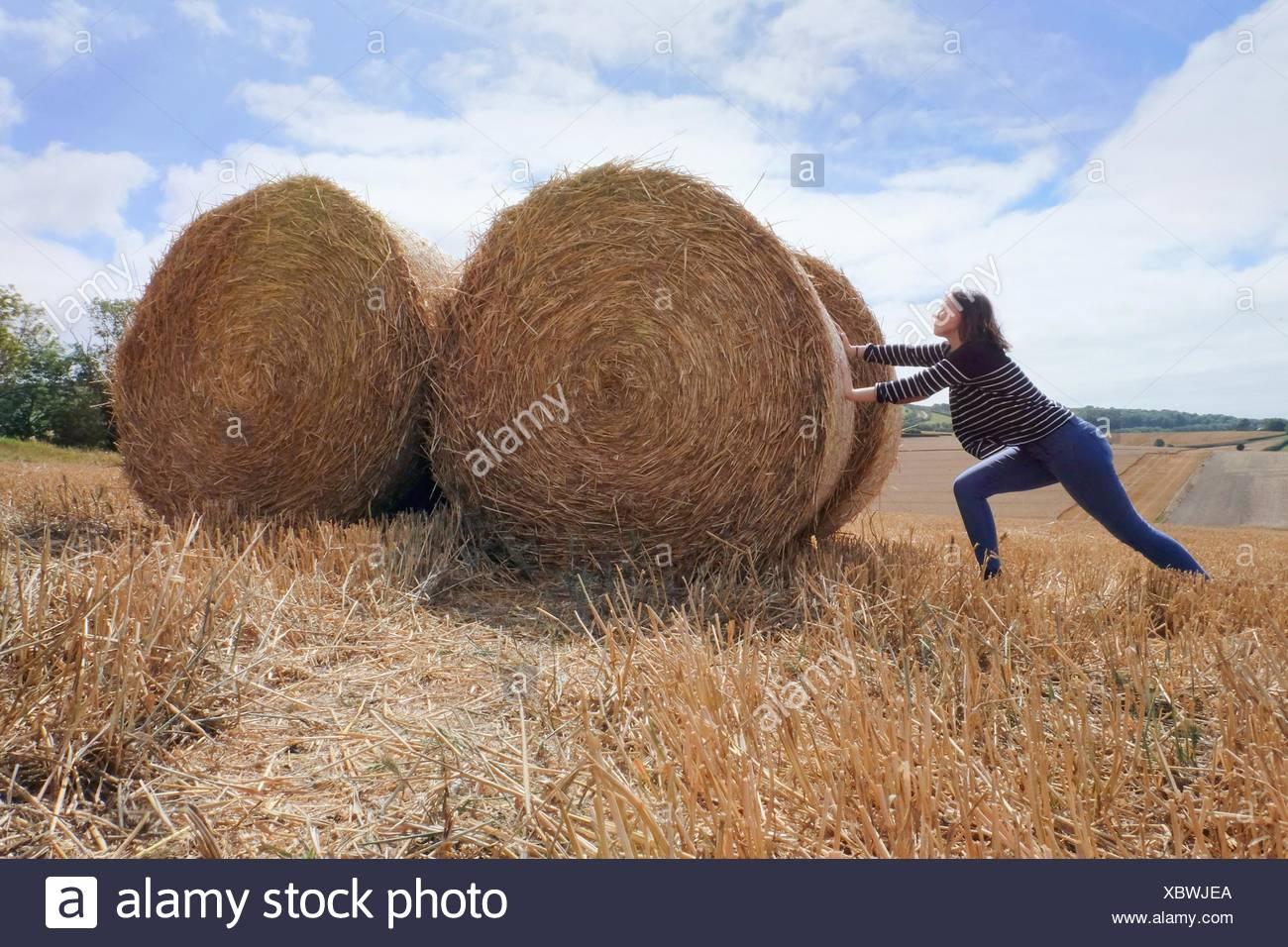 Mujer joven pretendiendo empujar montones de heno en el campo cosechado Foto de stock