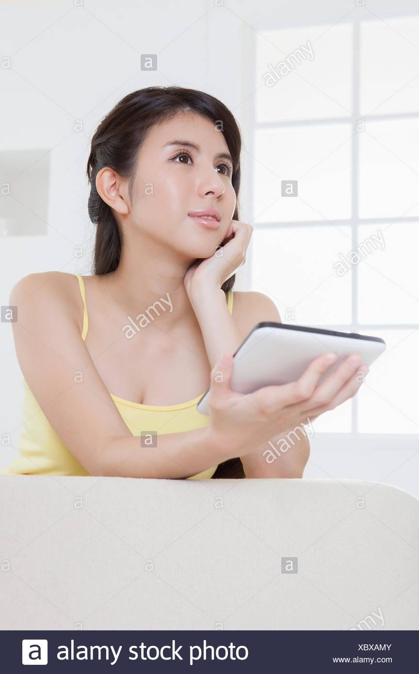 Mujer joven sosteniendo la almohadilla táctil y apartar la mirada, Imagen De Stock