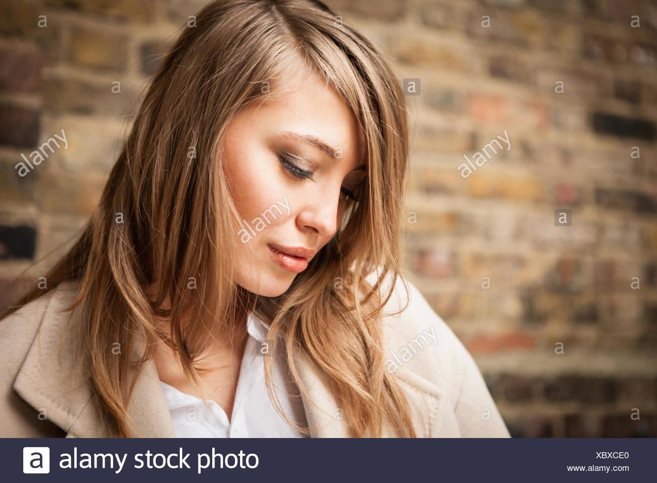Mujer con alicaído ojos, pared de ladrillo en segundo plano. Imagen De Stock