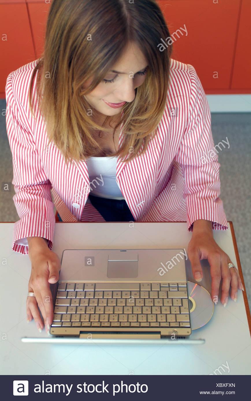 Hermosa mujer joven con el pelo largo, poniendo un CD en su ordenador portátil Imagen De Stock