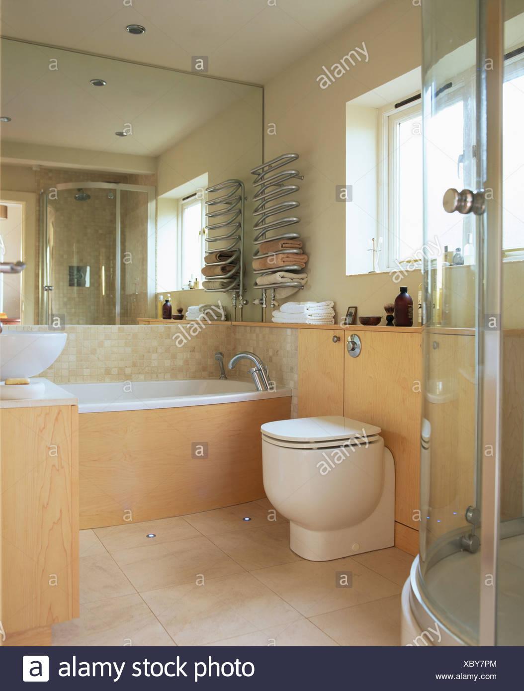 Pared con espejos sobre la bañera en el cuarto de baño moderno con ...