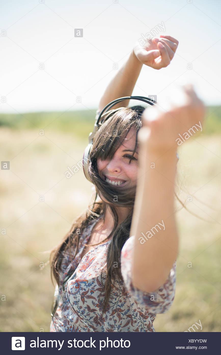 Retrato de mujer adulta media bailando en el campo con los brazos levantados, usando audífonos Imagen De Stock