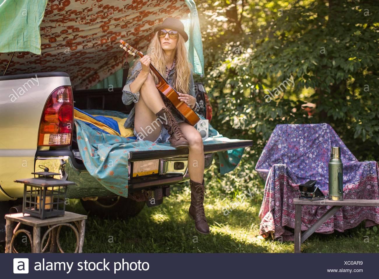 Chica jugando ukulele mientras camping en pick up boot Imagen De Stock