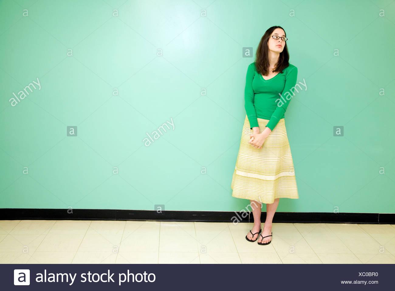 Mujer joven contra una pared verde Imagen De Stock