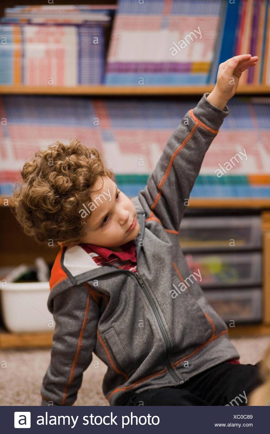 Niño levantando la mano en el aula Imagen De Stock