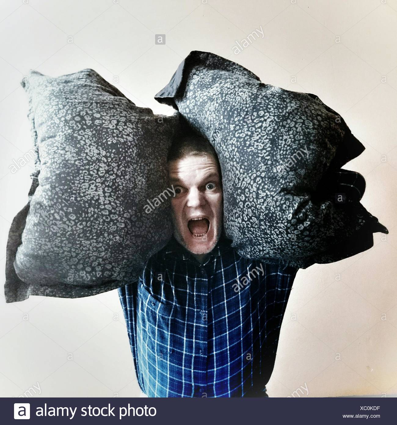 Retrato del hombre gritando mientras llevaba almohadas contra el fondo blanco. Foto de stock