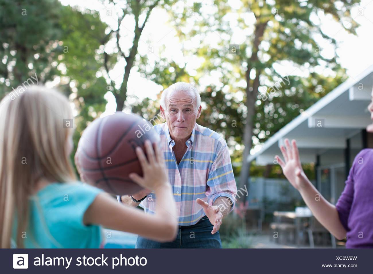 Older Man jugar al baloncesto con nietas Imagen De Stock