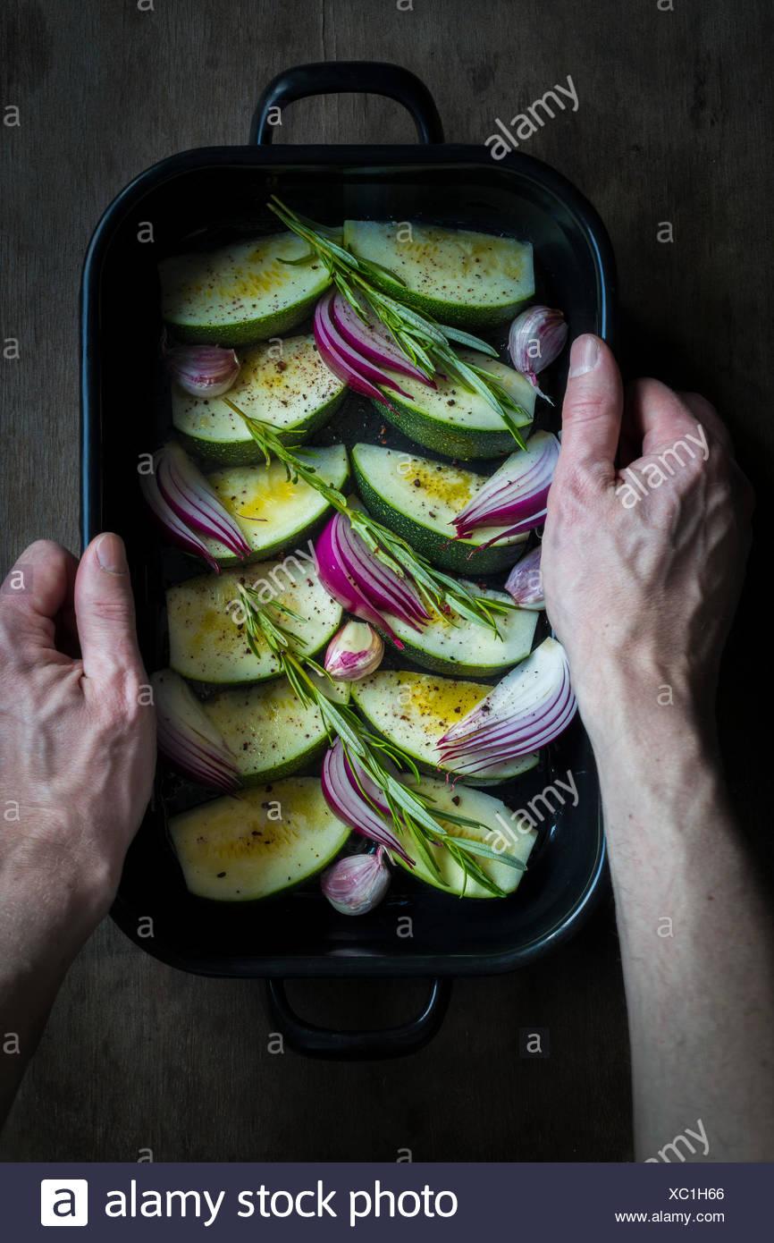 Manos sosteniendo un plato para horno con calabacines, cebollas y hierbas frescas preparadas para cocinar Imagen De Stock