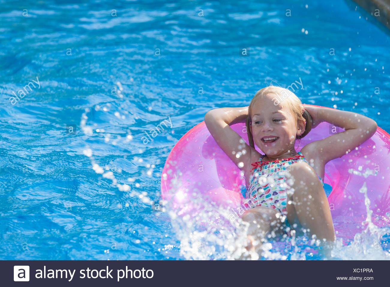 Chica acostada sobre su espalda en anillo inflable en el jardín piscina Imagen De Stock
