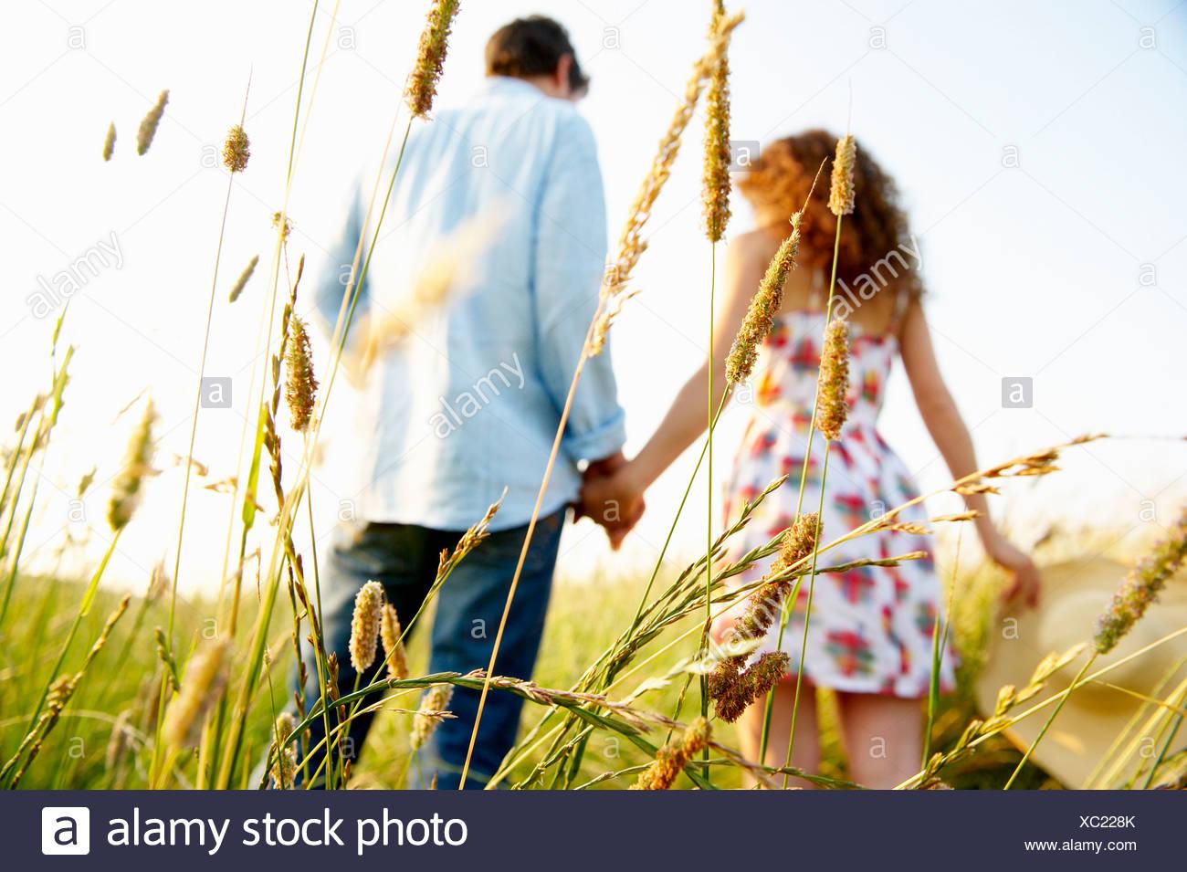 Las manos de la pareja en un campo de trigo Imagen De Stock
