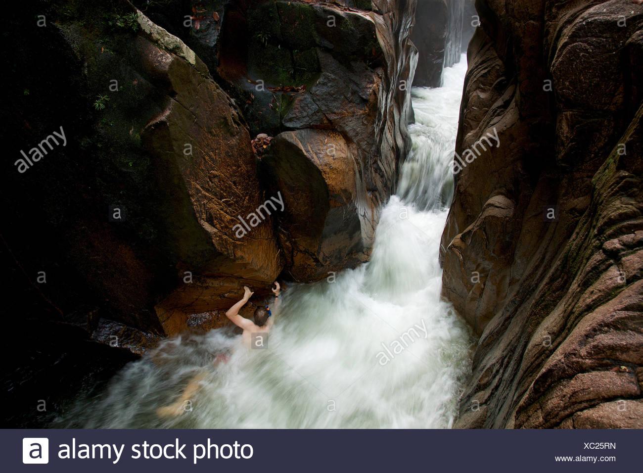 El agua brota a través Riam, o el canal Parit Falls, una inusual la ranura en la parte superior de la cascada Río Siduk. Imagen De Stock