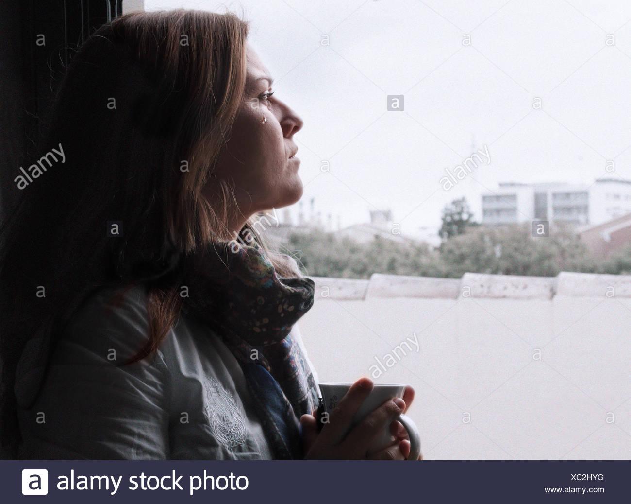 Llorar mujer mirando a través de la ventana Imagen De Stock