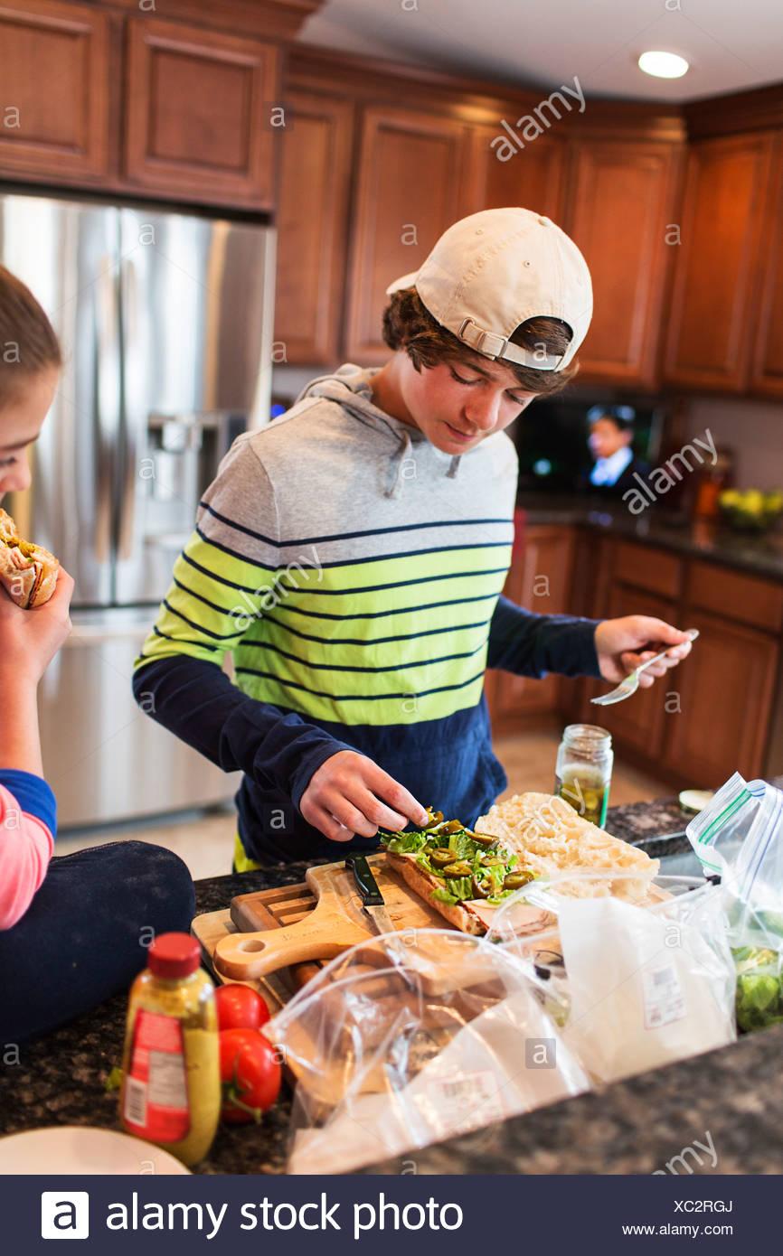 Hermano y hermana en la cocina preparando sandwich Foto de stock