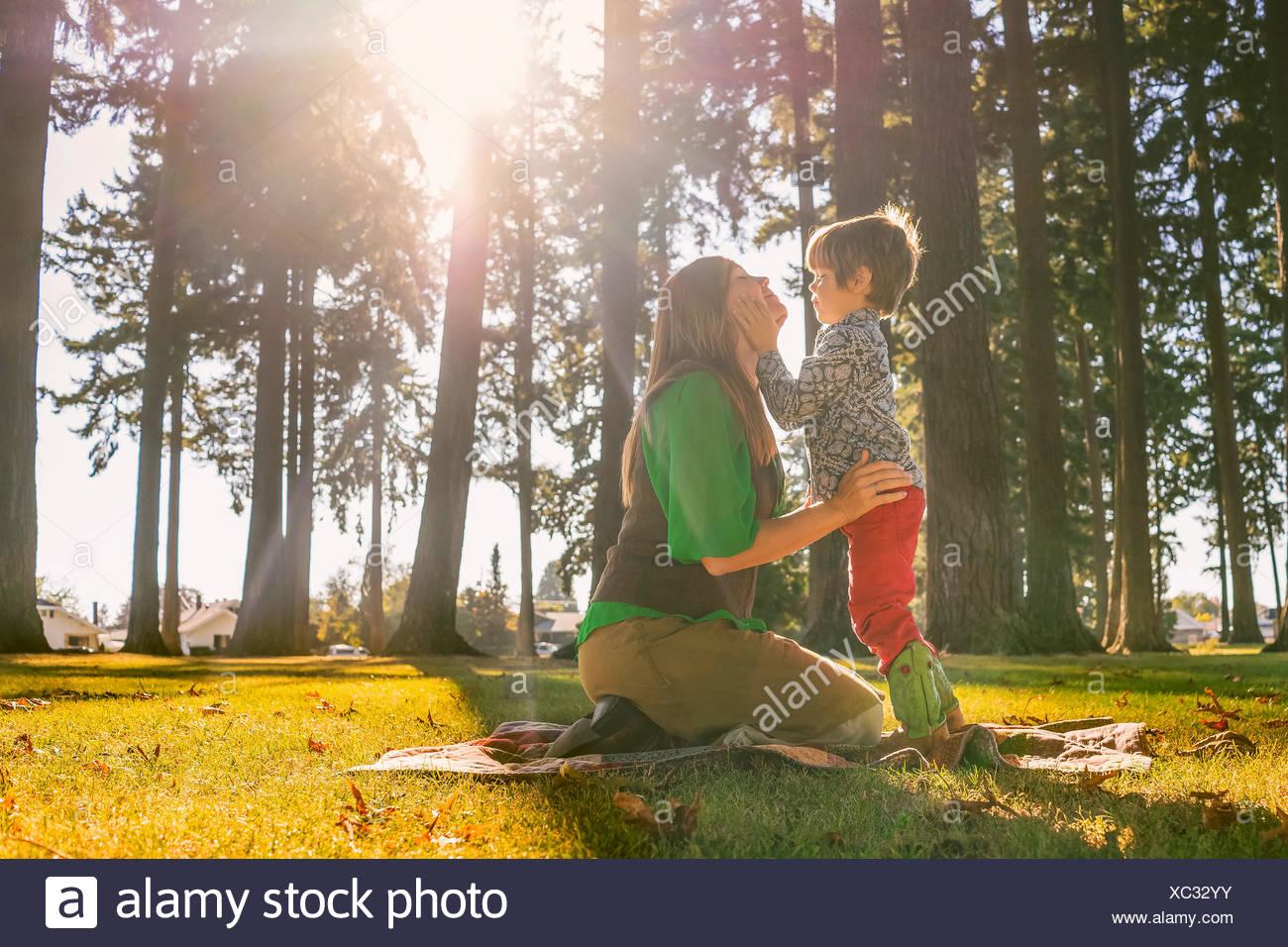 Madre e hijo tocando con caras sonrientes Foto de stock