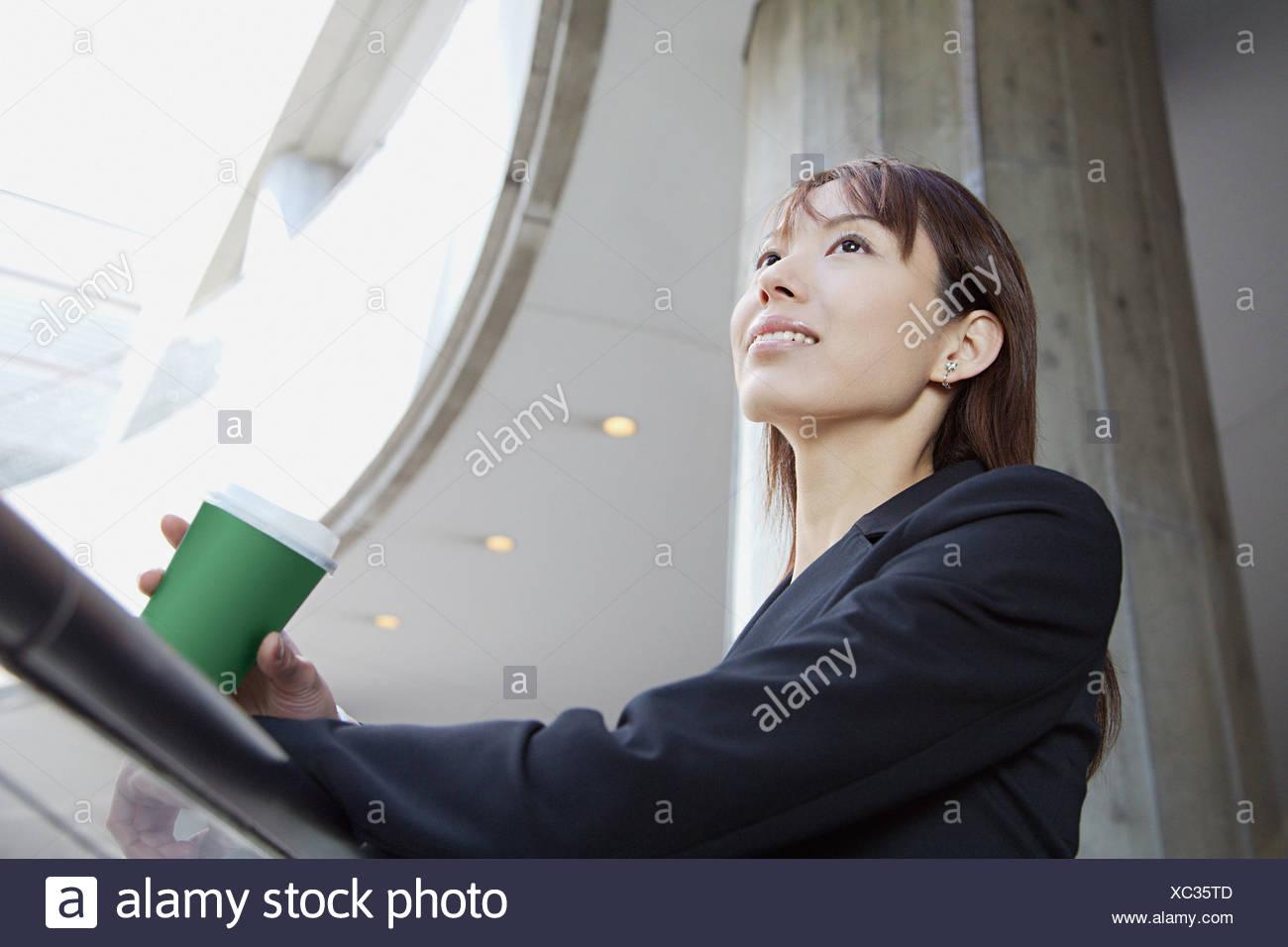 Mujer en una escalera con taza de café Imagen De Stock