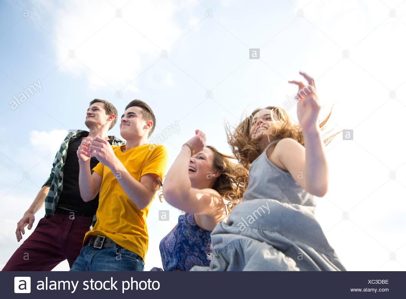 Grupo de jóvenes adultos, correr al aire libre, vista de ángulo bajo Imagen De Stock