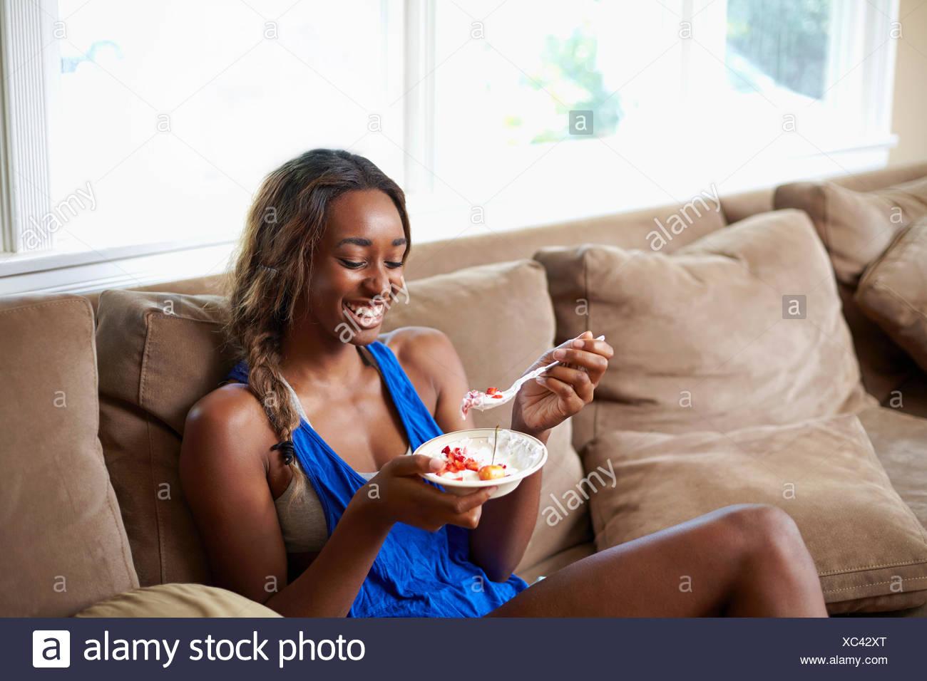Mujer joven tomando un salto de entrenamiento, comer fruta en el sofá Imagen De Stock