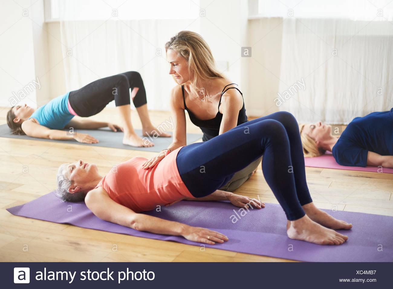 Apoyo docente alumno tumbado en vuelta en clase de pilates Imagen De Stock