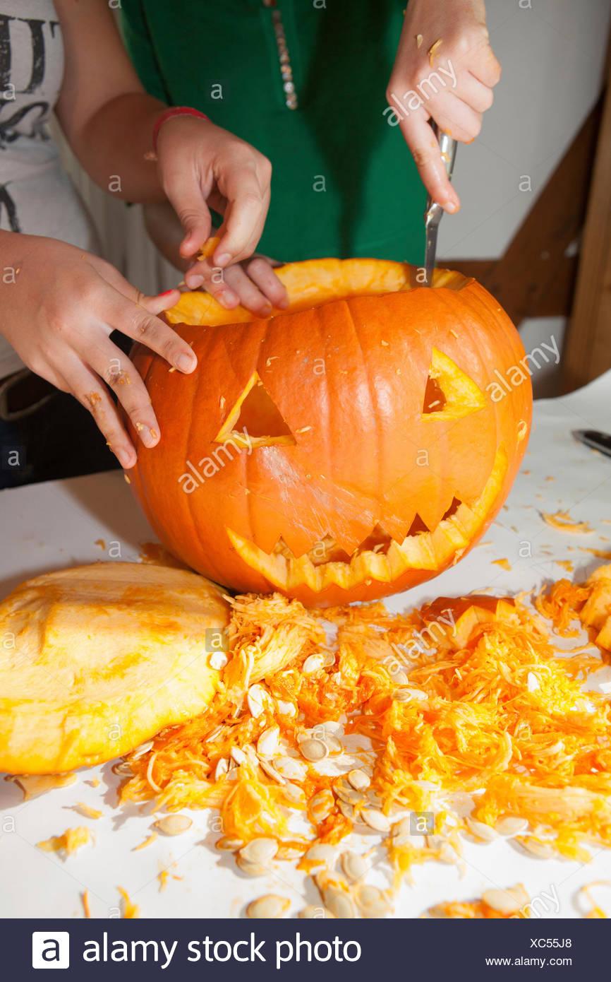 Dos niñas, de unos 14 años, un rostro tallado en una calabaza de Halloween Foto de stock