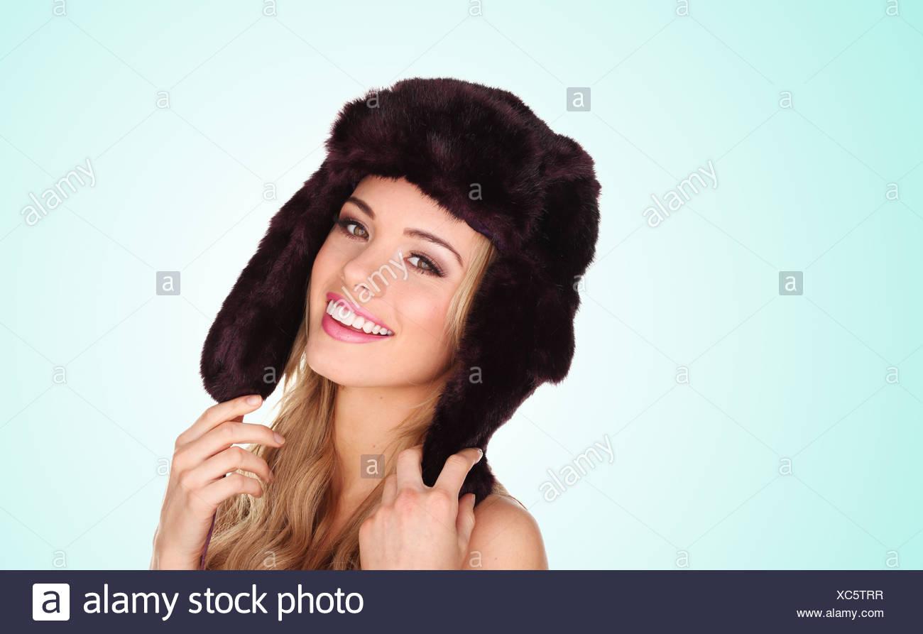 Atractiva mujer joven vistiendo un sombrero de piel de invierno con orejeras  dando una bella sonrisa 280c236dc74