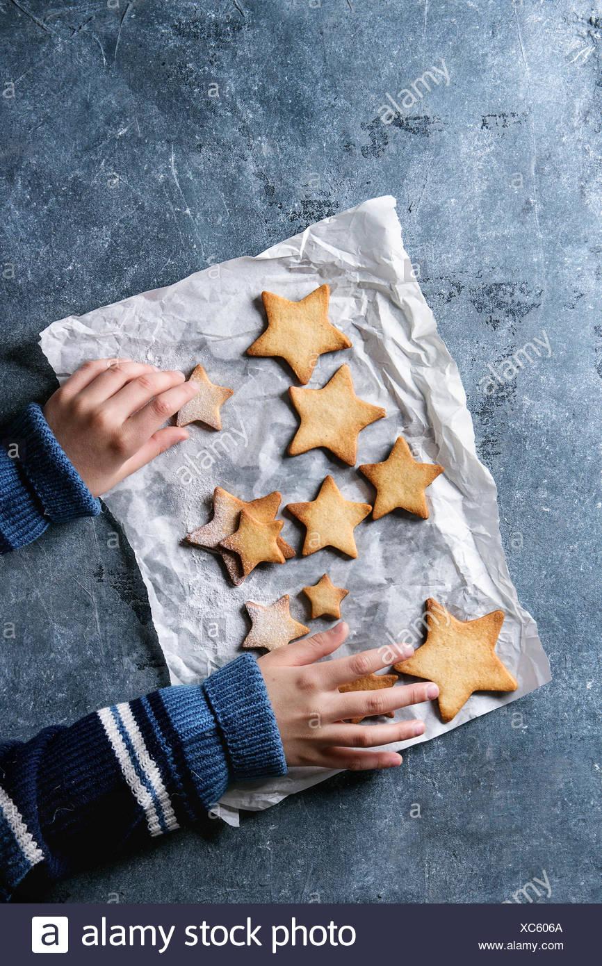 Las manos del niño en suéter de lana tomar navidad galletas caseras galletas de azúcar en forma de estrella de diferentes tamaños con azúcar en polvo de hornear sobre papel azul Imagen De Stock