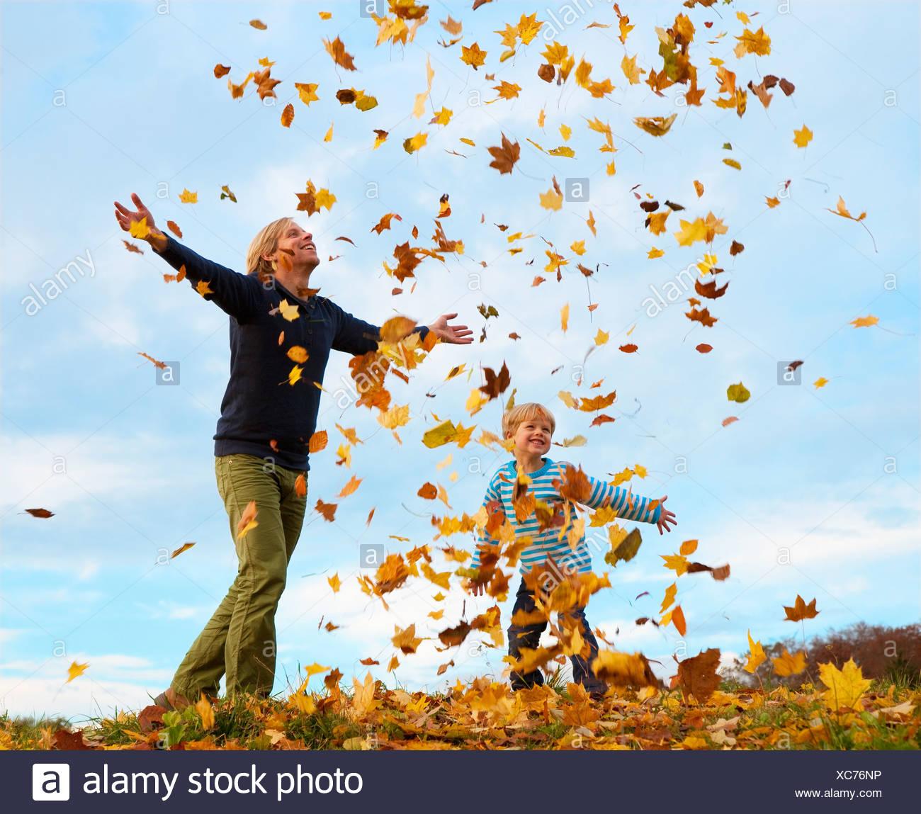 Padre e hijo jugando en hojas de otoño Foto de stock