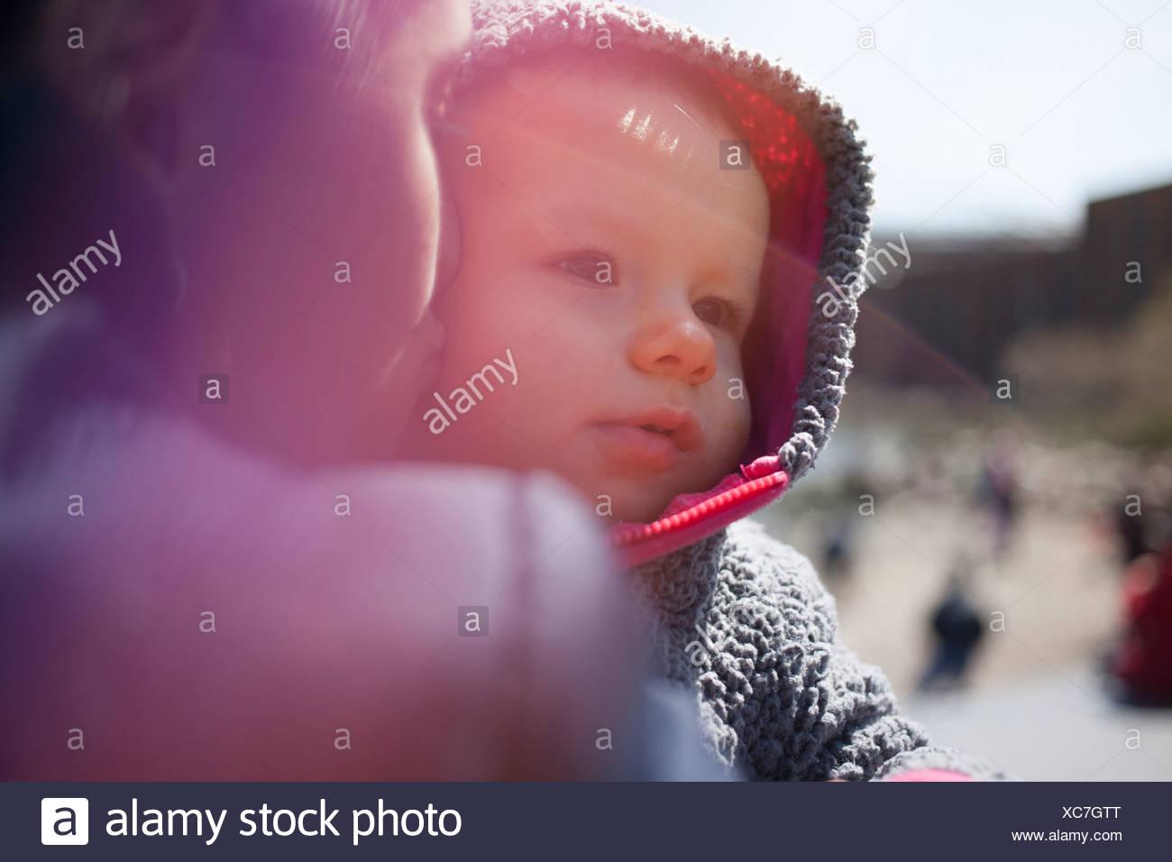 Madre sosteniendo hija vistiendo el capó Imagen De Stock