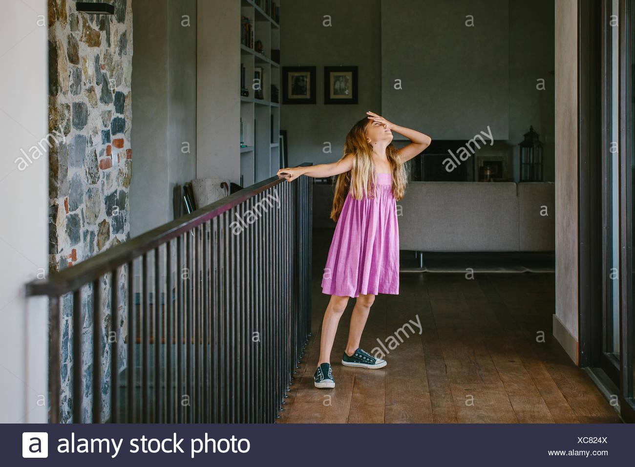 Chica en el aterrizaje con la mano sobre la frente Imagen De Stock