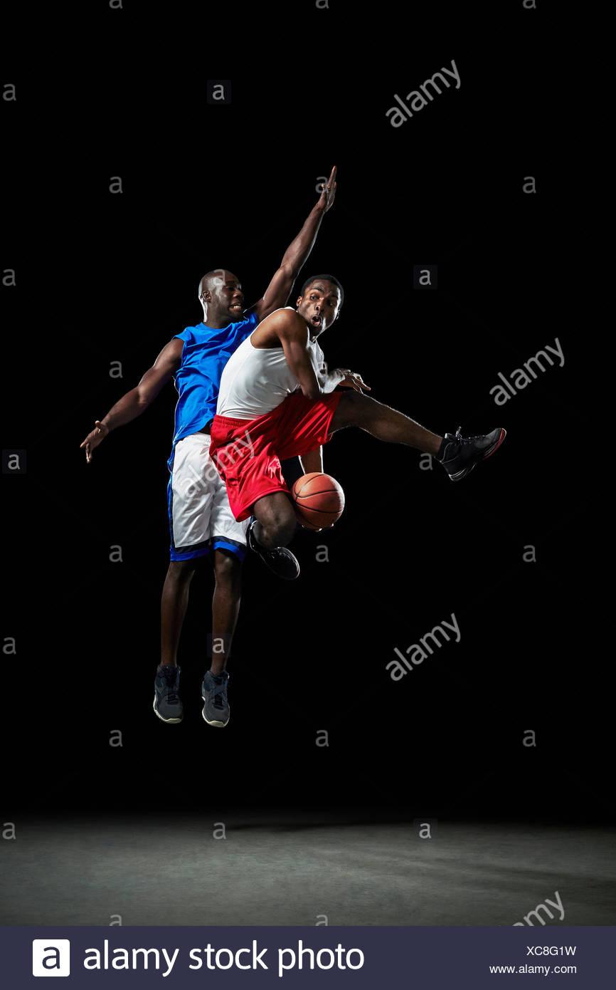 Jugadores de baloncesto masculino de saltar y disparar la bola Imagen De Stock