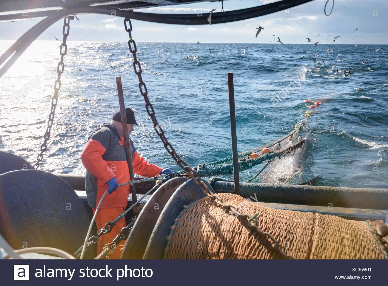 Tendiendo redes de pescador arrastrero Foto de stock