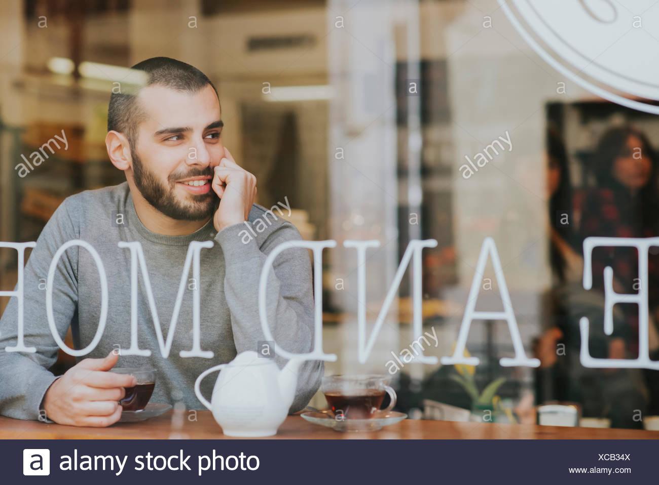 Joven sentado en la cafetería, ver a través de la ventana Foto de stock