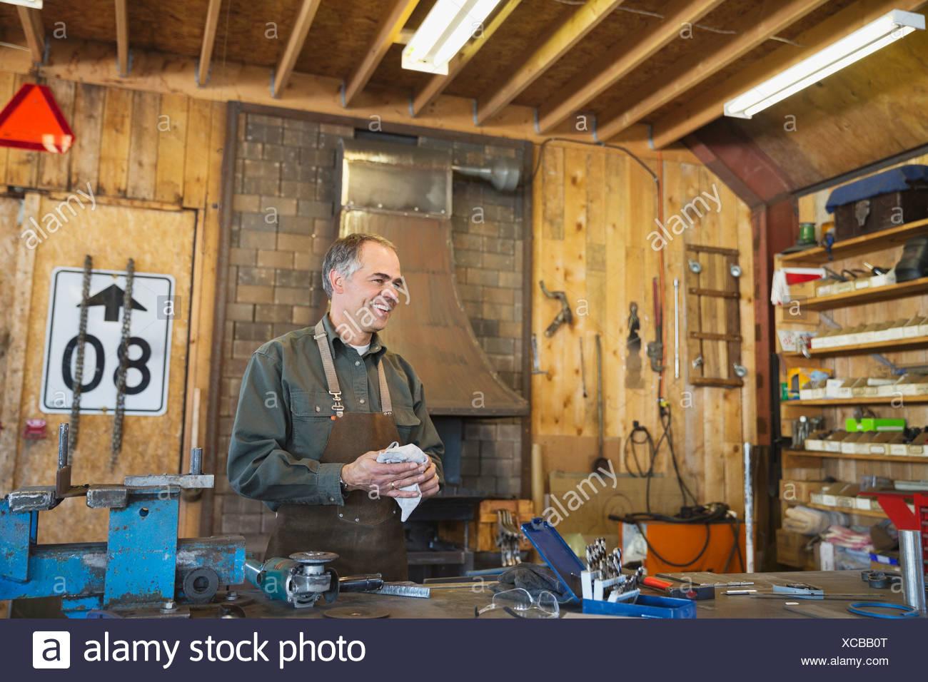 Obrero metalúrgico limpieza en workbench Imagen De Stock