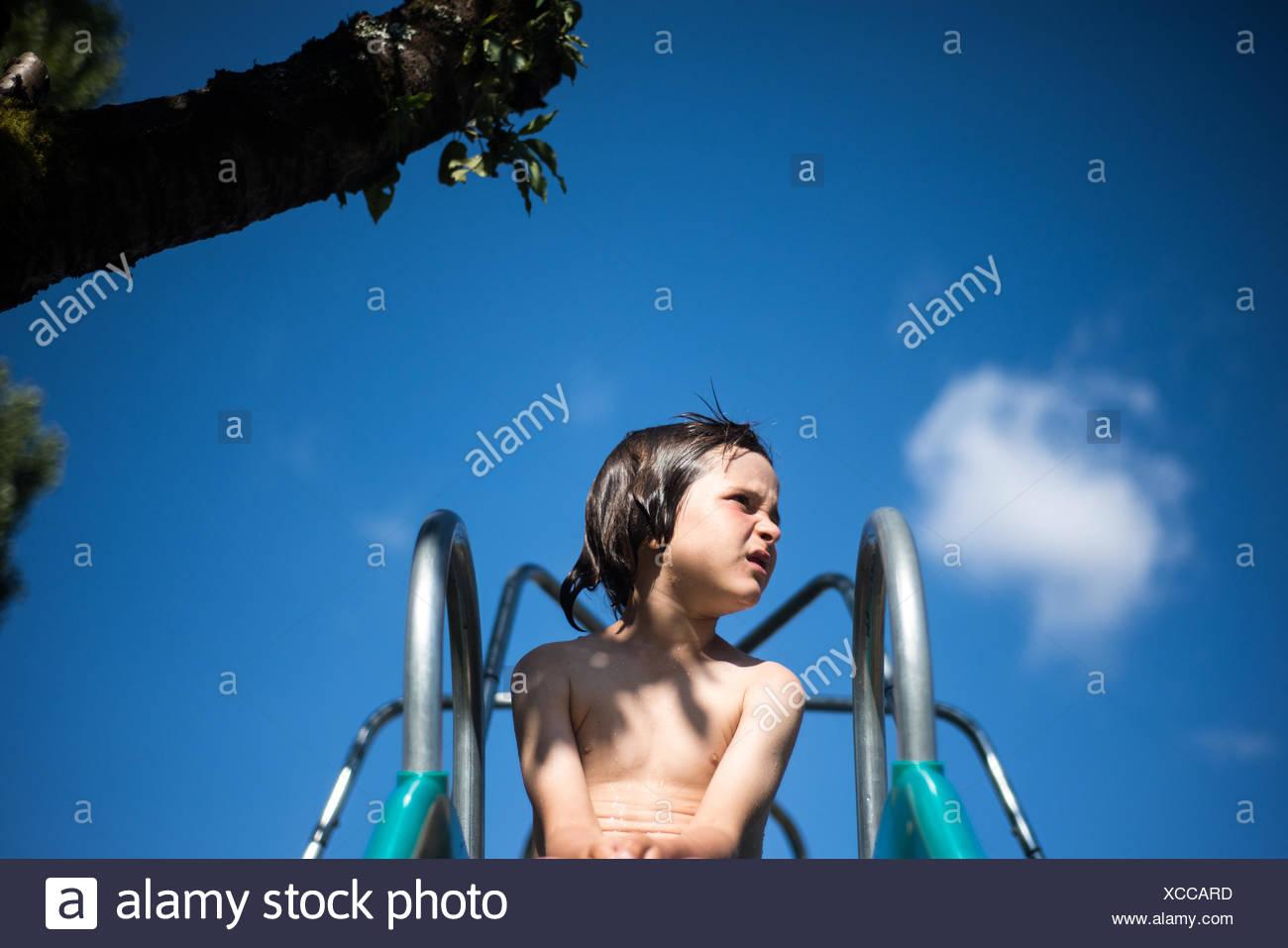 Chico en la parte superior de la diapositiva patio mirando lejos Imagen De Stock