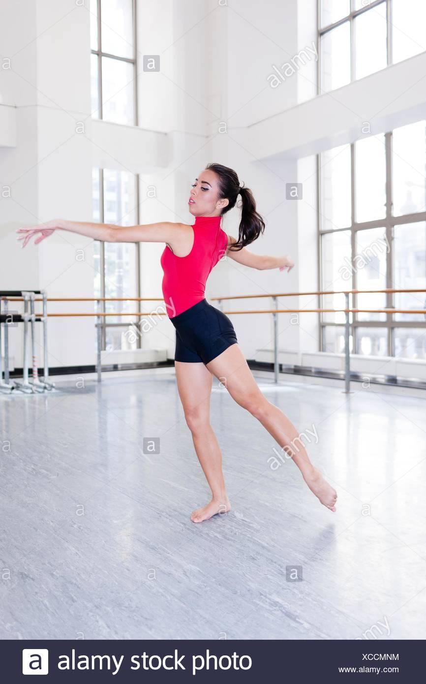 Mujer joven en el estudio de baile baile brazos abiertos mirando lejos Imagen De Stock