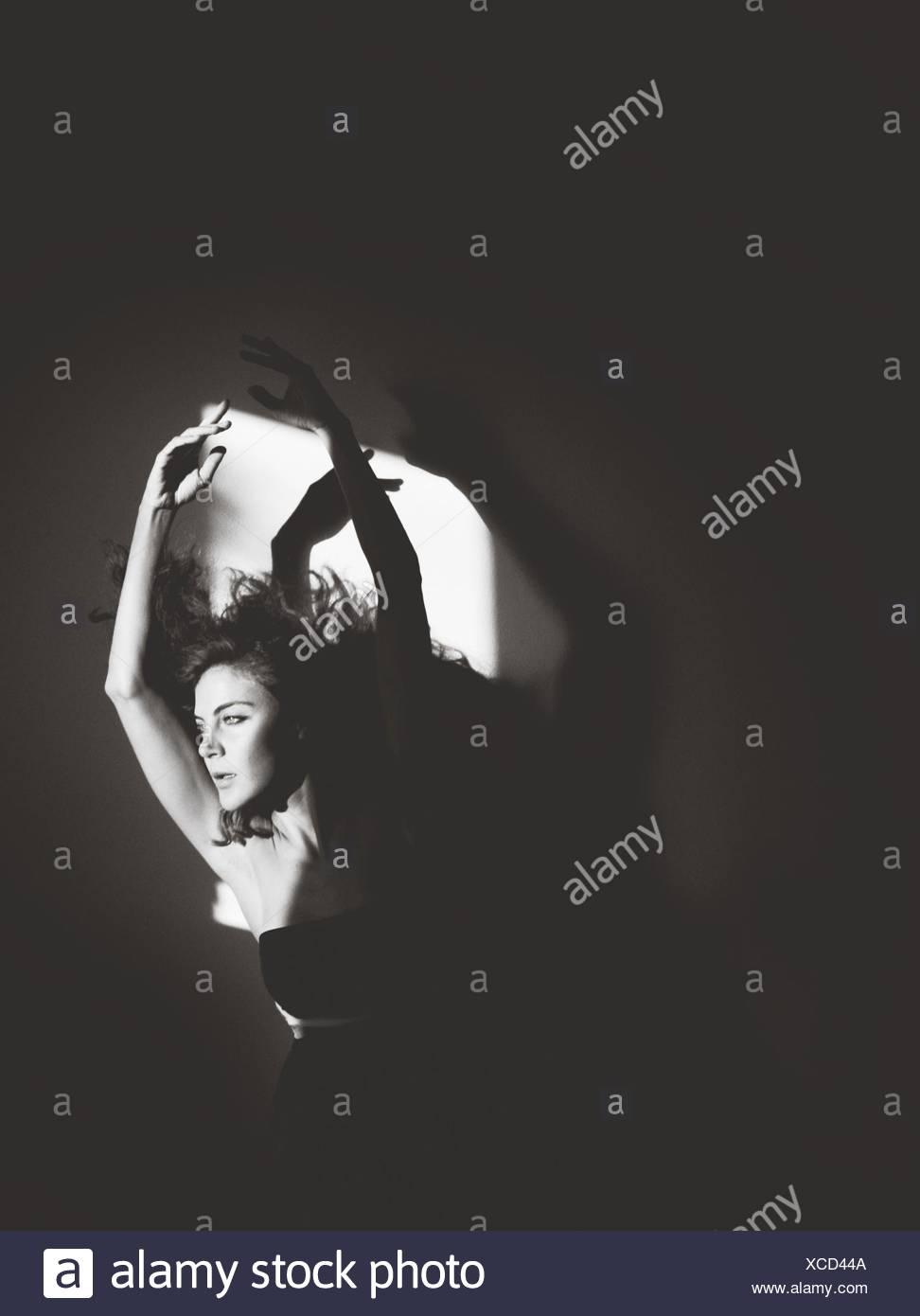 Retrato de mujer joven con los brazos levantados Imagen De Stock
