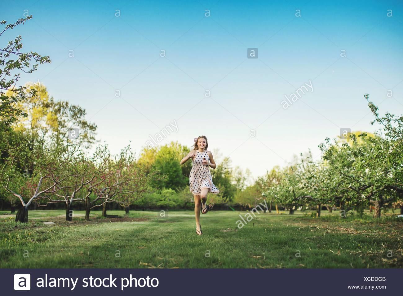Vista frontal de la longitud completa de la joven mujer vistiendo camisetas sin mangas vestido corriendo a través de la huerta, mirando a la cámara sonriendo Imagen De Stock