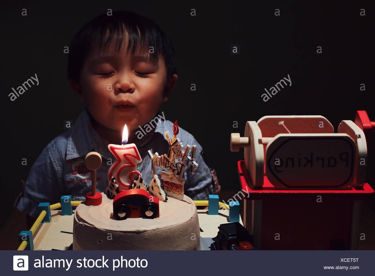 Chico lindo con ojo cerrado soplando vela de cumpleaños de tarta en cuarto oscuro Imagen De Stock