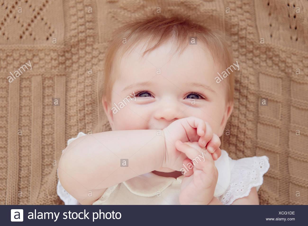 Close Up retrato de niña sonriente acostada sobre una manta Imagen De Stock