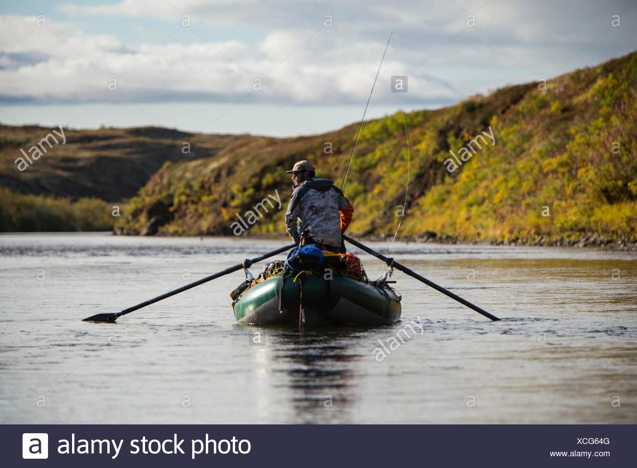 Un hombre analiza el agua para el salmón, mientras que el remo su balsa abajo un arroyo sin nombre en el oeste de Alaska. Imagen De Stock