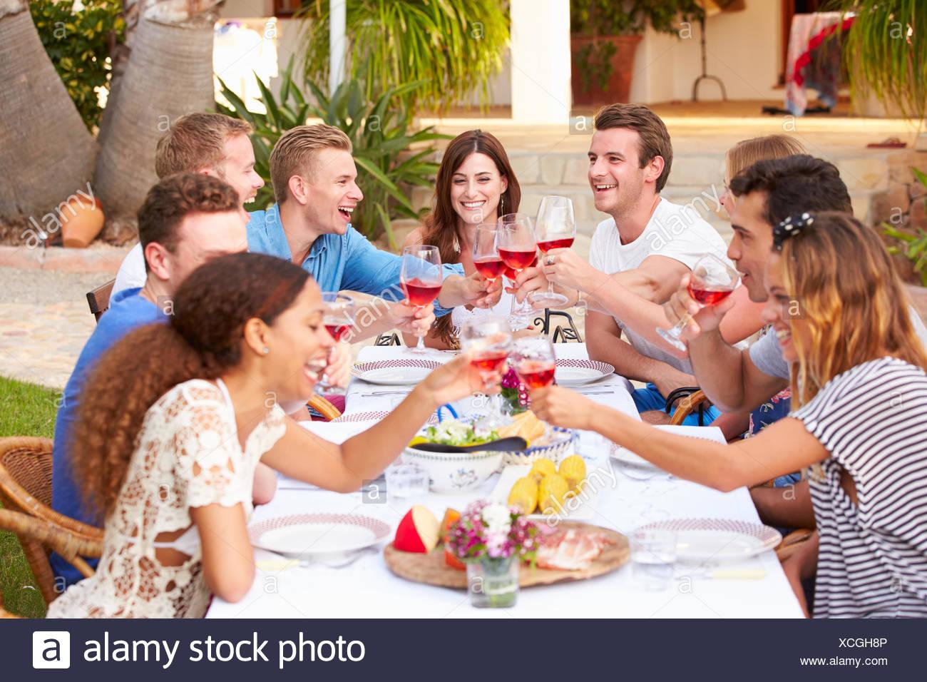 Grupo numeroso de jóvenes amigos, disfrutando de comidas al aire libre juntos Foto de stock
