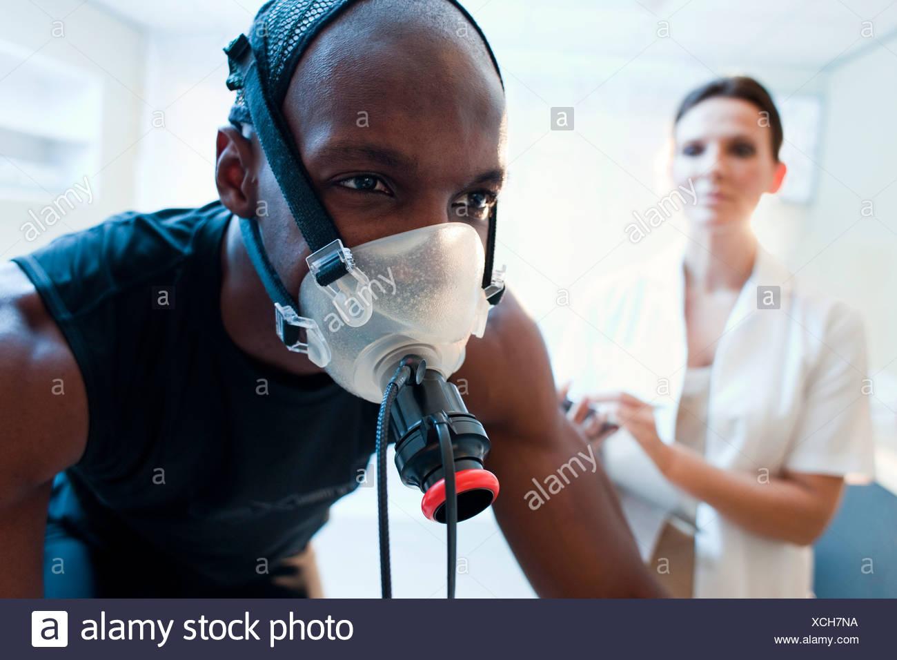 Pruebas de rendimiento liberados modelo deportista montando una bicicleta de ejercicio mientras su rendimiento y el consumo de oxígeno se miden Imagen De Stock