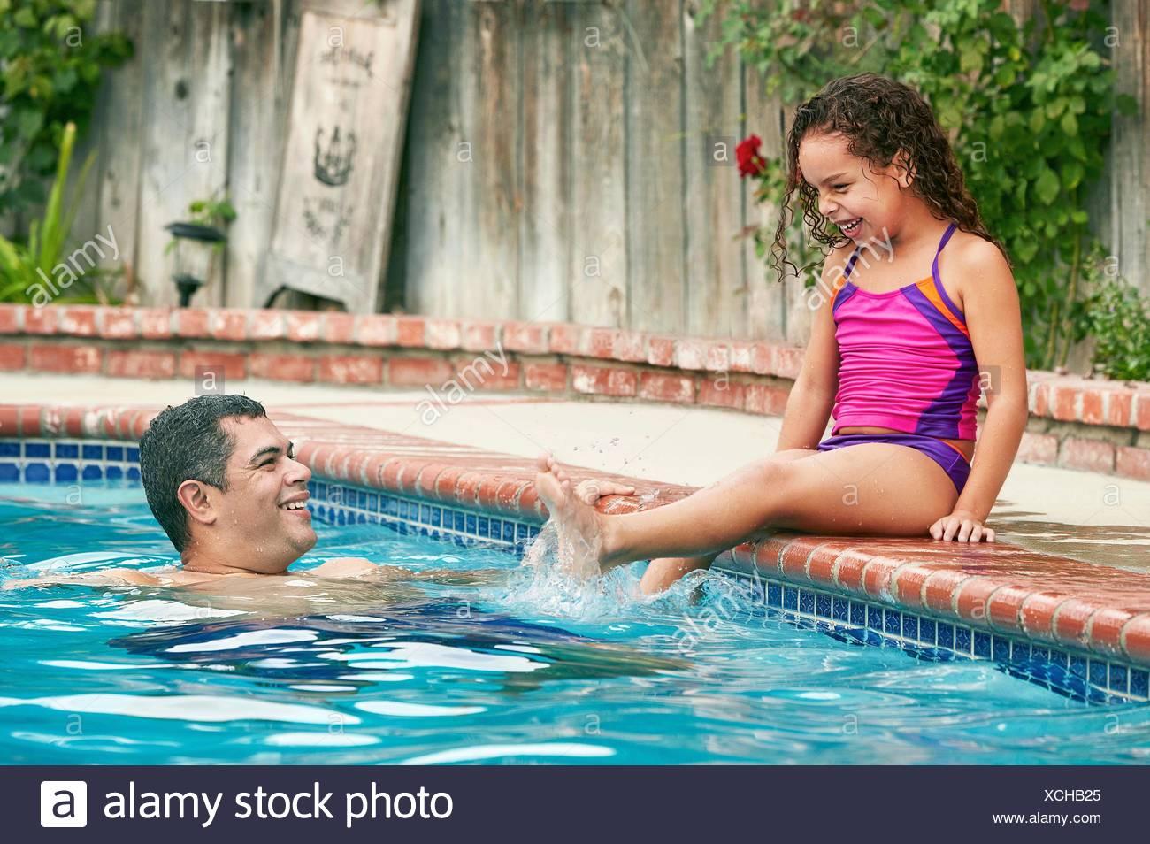 Vestida de traje de baño sentado al lado de la piscina salpicando padre sonriendo Imagen De Stock