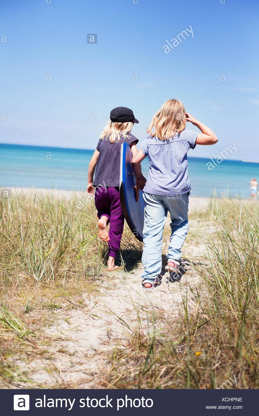 Suecia, Gotland, Faro, dos niñas (8-9, 10-11) caminar en la playa Imagen De Stock