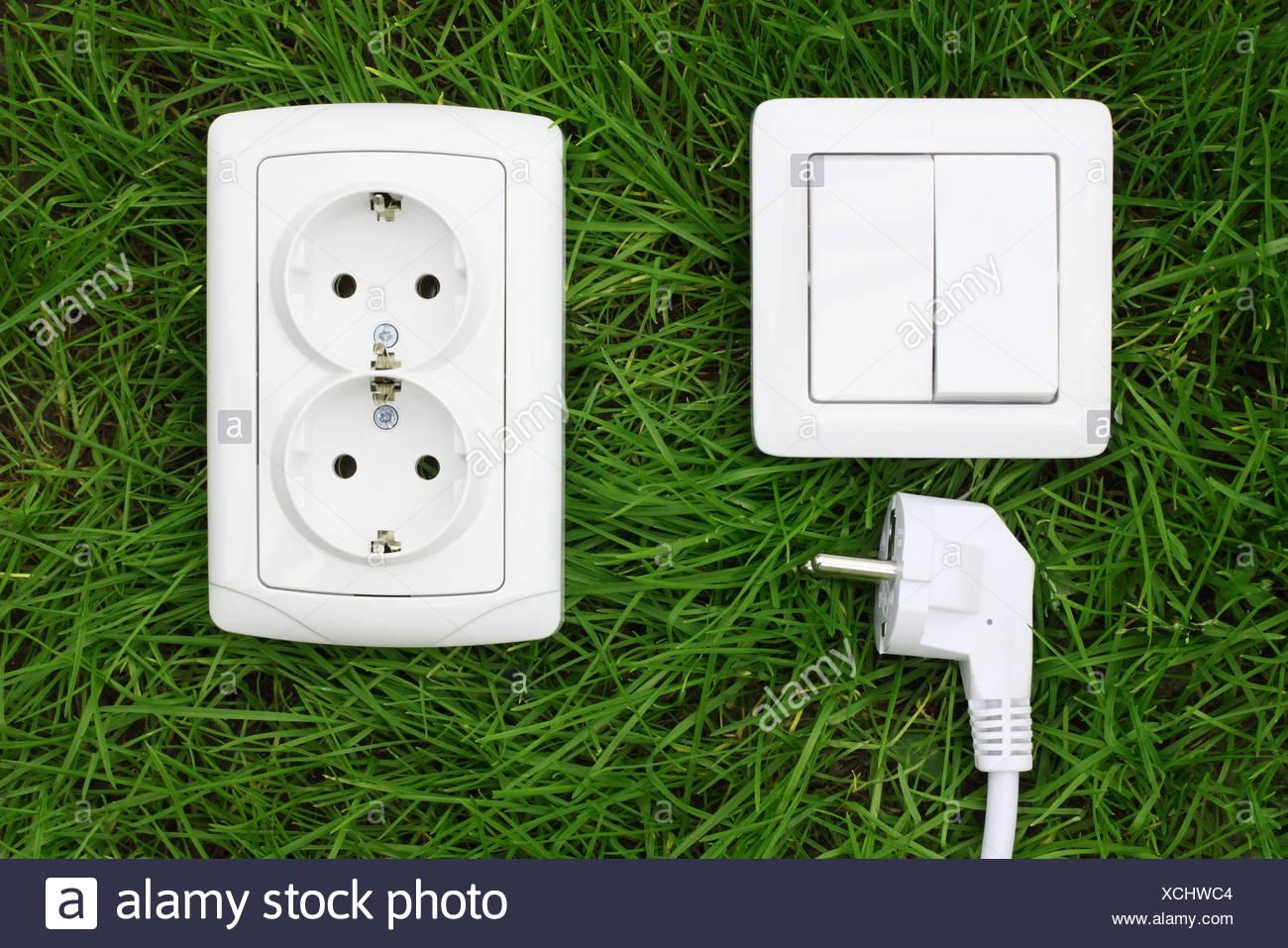 Receptáculo de alimentación y el interruptor de luces sobre un césped verde Foto de stock