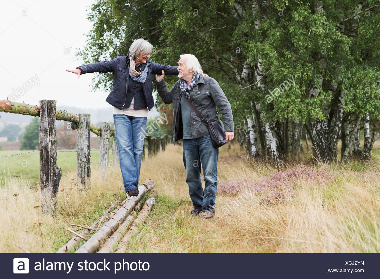 Las parejas ancianas, mujer equilibrio sobre troncos Foto de stock